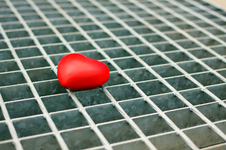 Red heart on a metal grid
