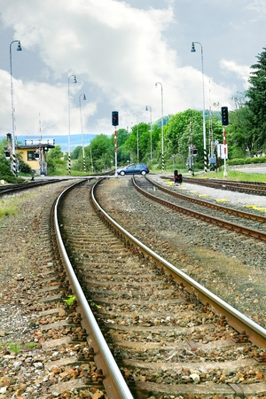 complicated journey: Railroad tracks with crossing and clouds