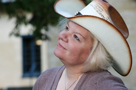 grins: Woman Wearing Cowboy Hat Looks Up and Grins