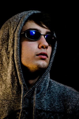 Teenager Poses While Wearing Hood and Sunglasses Stock Photo