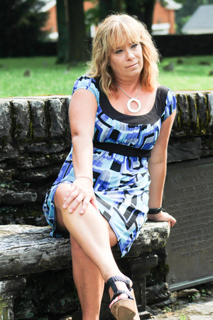fourties: Woman With Legs Crossed Sitting on Bench Stock Photo
