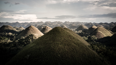 chocolaty: The chocolate hills are Bohols mystical limestone formations that are covered with grass that sometimes is green and at other times chocolaty brown or with the help of the filter white chocolate. Stock Photo