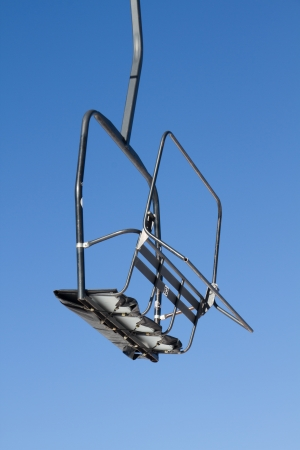 Empty chair of a skilift against a blue Colorado sky