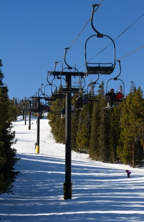 Skiers riding a double chairlift back to the top of the mountain, on a beautiful day of downhill skiing just outside of Boulder, Colorado photo