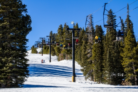 denver: Skiers riding a double chairlift back to the top of the mountain through the trees at a Colorado Ski Resort Stock Photo