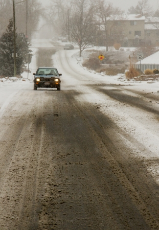 A small car drives down a deserted city street during the season's first snow storm in Denver, Colorado photo
