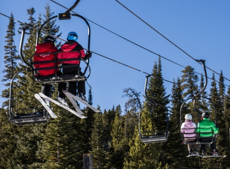 rocky mountains colorado: Downhill skiers ride the double chairlift up the hill