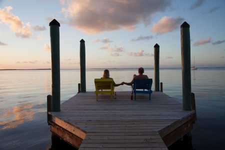 Couple sits on dock and dreams of the future while watching a beautiful sunset