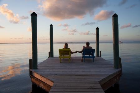 gaze: Echtpaar zit op dok en dromen van de toekomst tijdens het kijken naar een prachtige zonsondergang Stockfoto