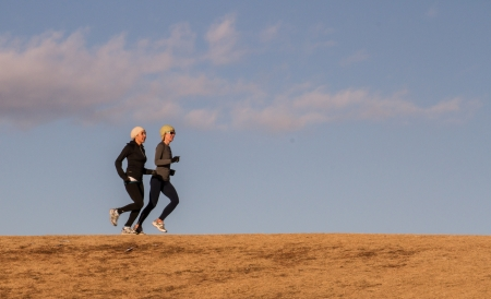 Trail runners practice for next race on grassy ridge with blue sky behind them