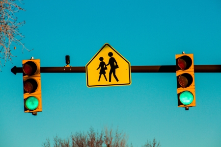proceed: Stop lights green for go at a school crossing intersection Stock Photo