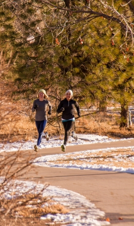 two young women jogging in the park, on a curved trail through trees in the winter with snow on the ground photo