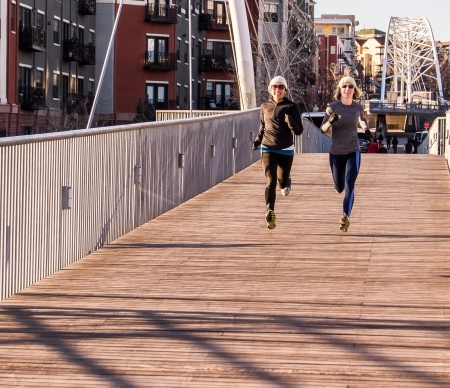 sweatshirts: two young women jogging in an urban setting crossing a bridge into downtown Denver Stock Photo