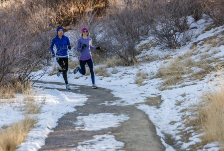 sweatshirts: two young women jogging in a park on a dirt trail in the winter with snow on the ground Stock Photo