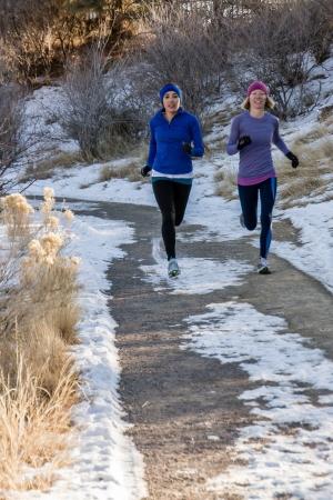 people jogging: dos mujeres j�venes corriendo en el parque, en un camino curvo a trav�s de los �rboles en el invierno con nieve en el suelo