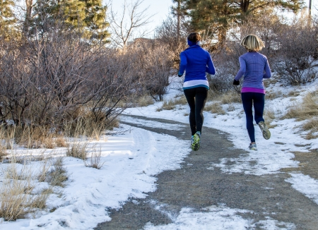 two young women jogging in the park, on a curved trail through trees in the winter with snow on the ground Banco de Imagens