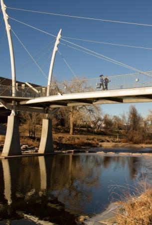 Runners crossing bridge over river in Denver photo