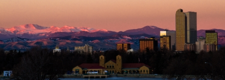 denver skyline with mountains: Denver skyline with pink sky at sunrise and mountains in background