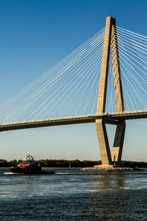 cooper: Ravenel Bridge taken from the Cooper river with a tug boat passing under the bridge