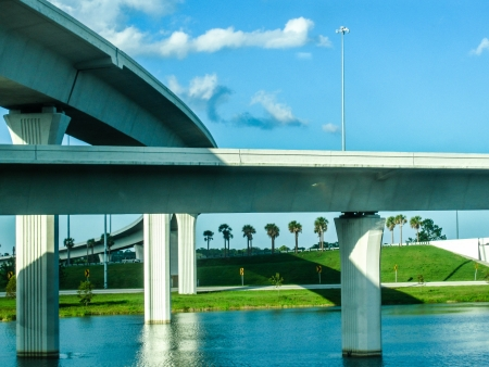 cement pole: Bridge and overpass in Florida with palm trees and water, interstate highway Stock Photo