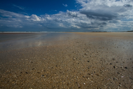 Low persective, wide angle shot of a deserted St  Augustine Beach with blue sky and gray clouds, yellow sand photo