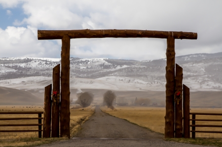 Big log gate over lane to Montana cattle ranch in the winter photo