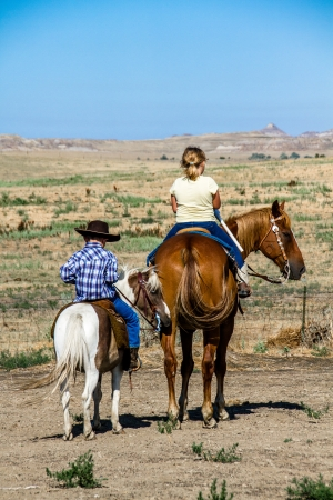 Young cowgirl and cowboy sitting on ponies under the clear blue sky photo