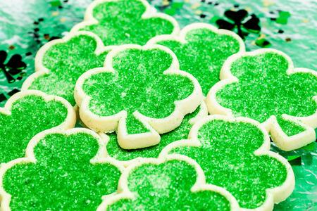 patron saint of ireland: Shamrock green sugar cookies on a green Saint Patrick\