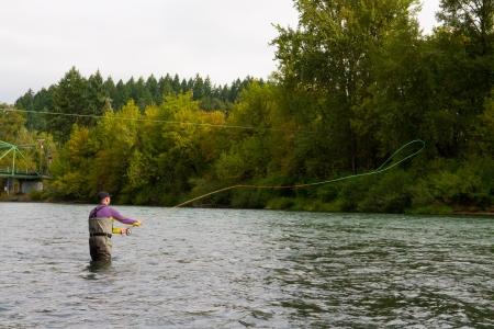 botas altas: A Spey casting cambios de pescador con mosca moscas de trucha arco iris en el río Willamette en Oregon.