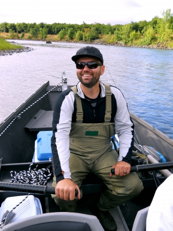 waders: river guide fishing in a boat