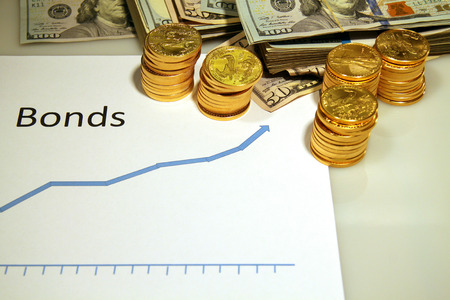 bonds: bonds rising up chart graph with gold money Stock Photo
