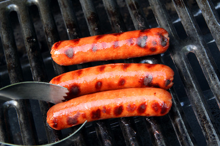 hot dogs on the grill with tongs