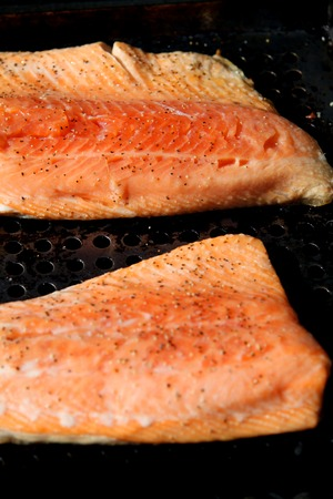partially: two salmon steelhead fillets partially cooked on the grill