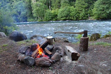 campfire with axe and coffee pot by river