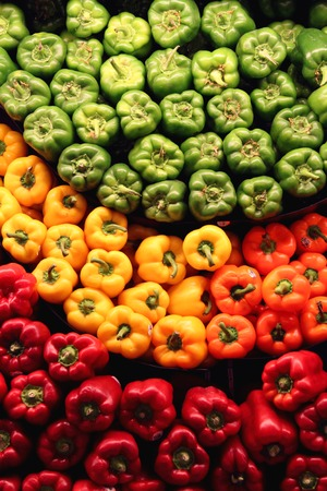 red green yellow orange peppers on display Stock Photo