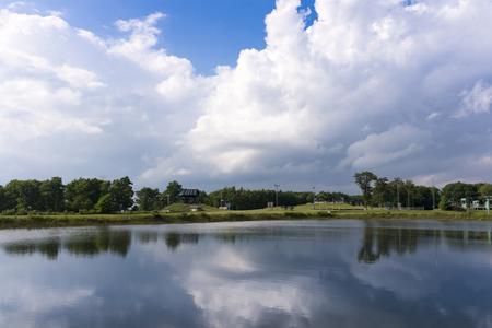 wispy: Bright white fluffy clouds reflect over a small mountaintop pond. Stock Photo