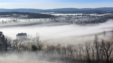 Wispy clouds and a dense fog blanket the early morning countryside in Deep Creek Lake, Maryland, United States.