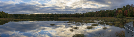 Puffy blue and white clouds are reflected in the still, mirror-like surface of a Virginia marshland. Meanwhile, green, orange, and red leaves adorn the trees in a surrounding forest.