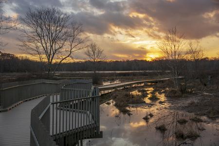 A wooden boardwalk winds through a barren marshland while a wonderful display of colors dance across the twilight sky. Reklamní fotografie