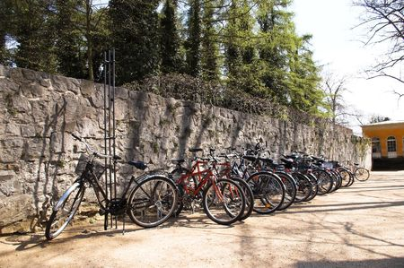 there is the parking for bicycles near the wall in the park