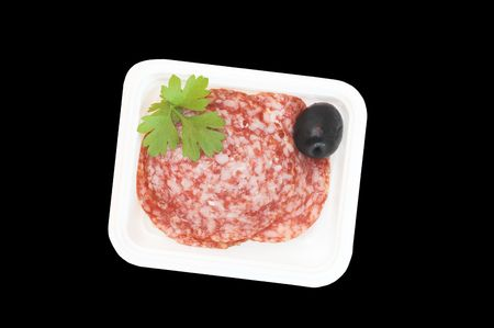 Slised salami in a plastik container, a part of breakfast in a plane. isolated, black, background.