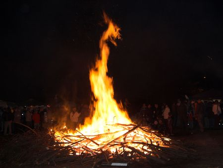 halloween, a crowd of people is celebrating around a fire