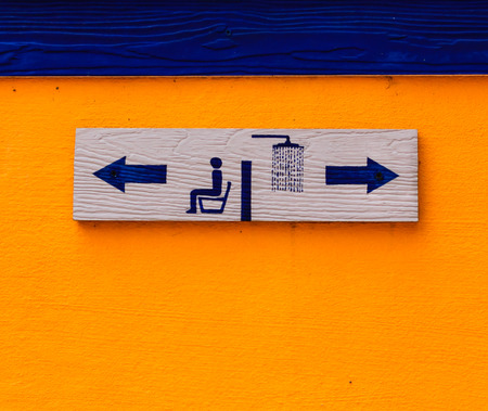 wood toilet sign on cement wall photo