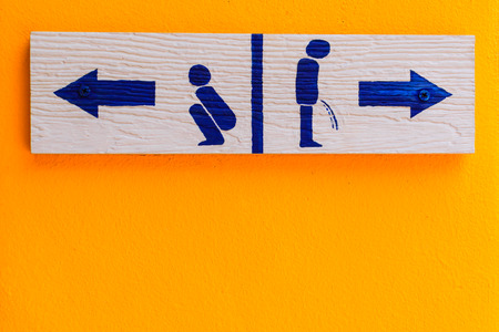 urinating: wood toilet sign on cement wall