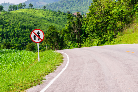 overtaking: No Overtaking  traffic sign board on national highway. because Steep Hill Descent and Winding Road