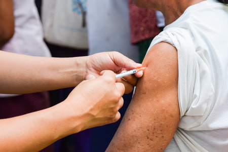 h1n1 vaccines: Doctor giving an injection to a patient