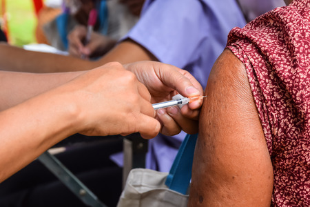 epidemiology: Doctor giving an injection to a patient