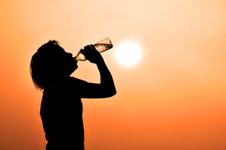 Silhouette of young woman drinking water  ( thirsty, hot feeling a need to drink water) Banque d'images
