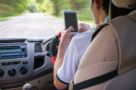 Driving while holding a mobile phone (cell phone use while driving) Stock fotó