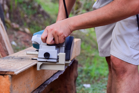 cut off saw: Building DIY table and chairs project , worker using hand held worm drive Power planer woodworking Tools Stock Photo